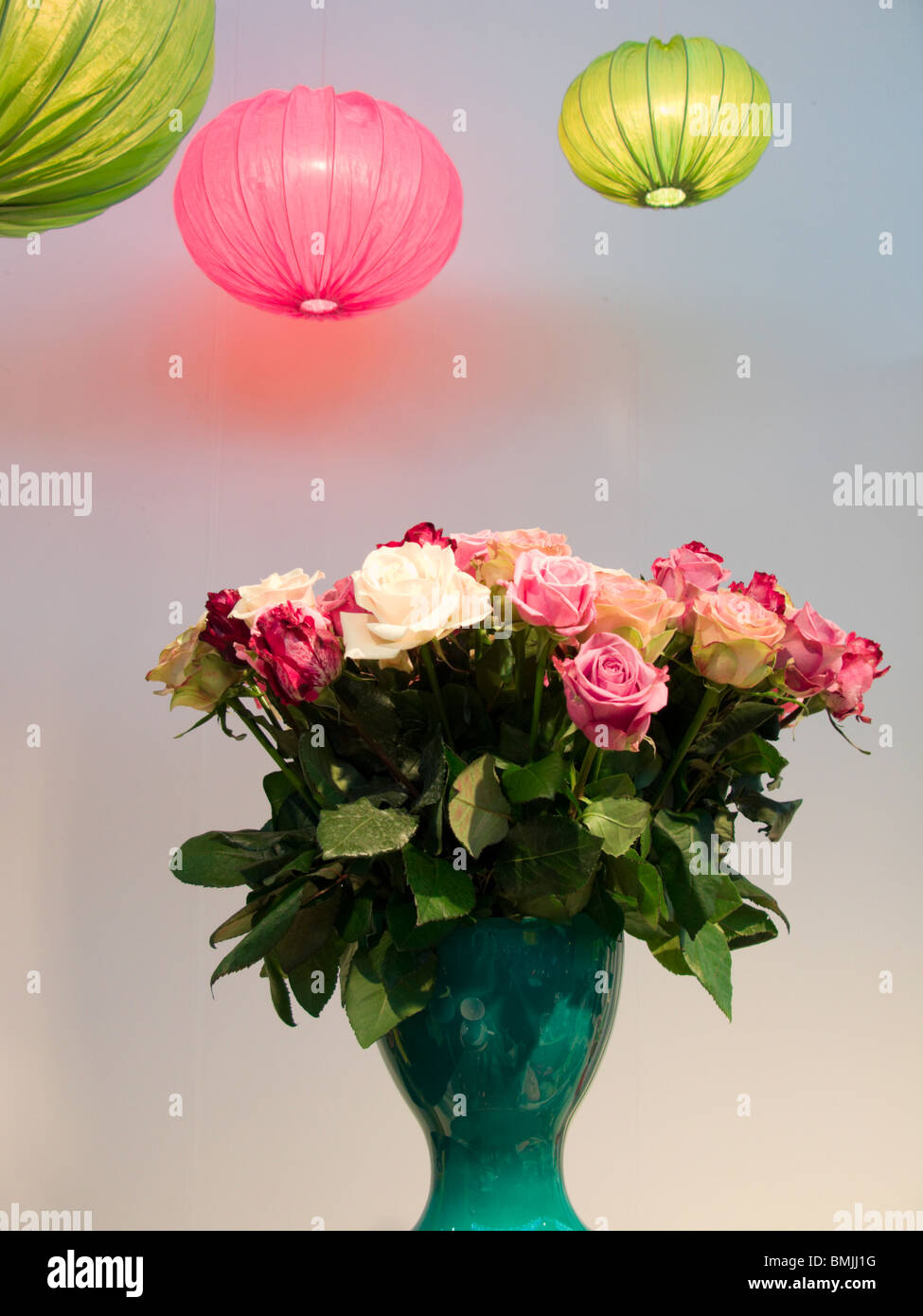 Pink and green ceiling lamps and roses in a vase, Sweden. - Stock Image