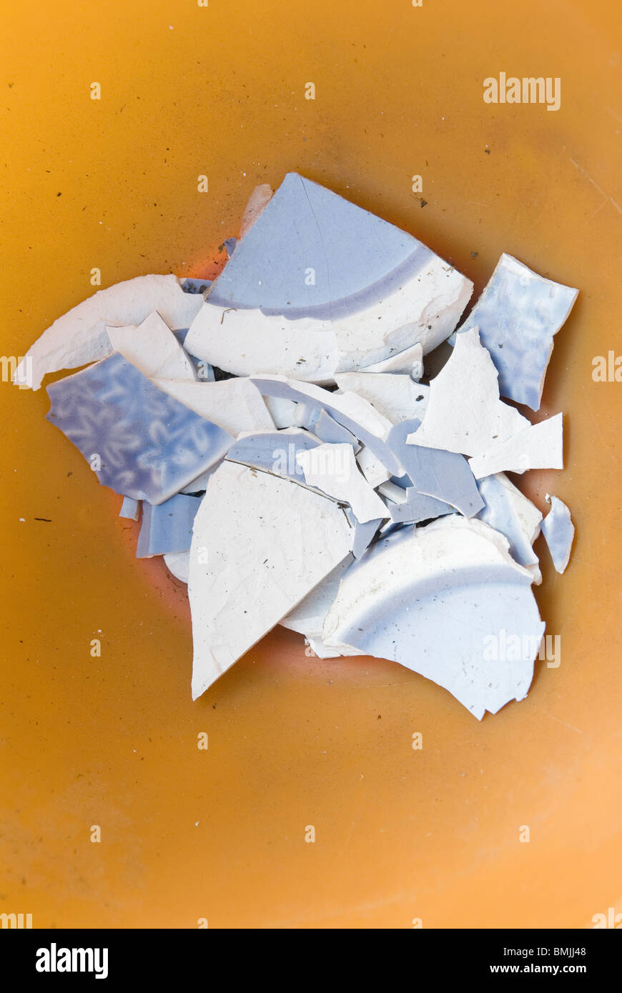 Broken pieces of flower pot on coloured background - Stock Image