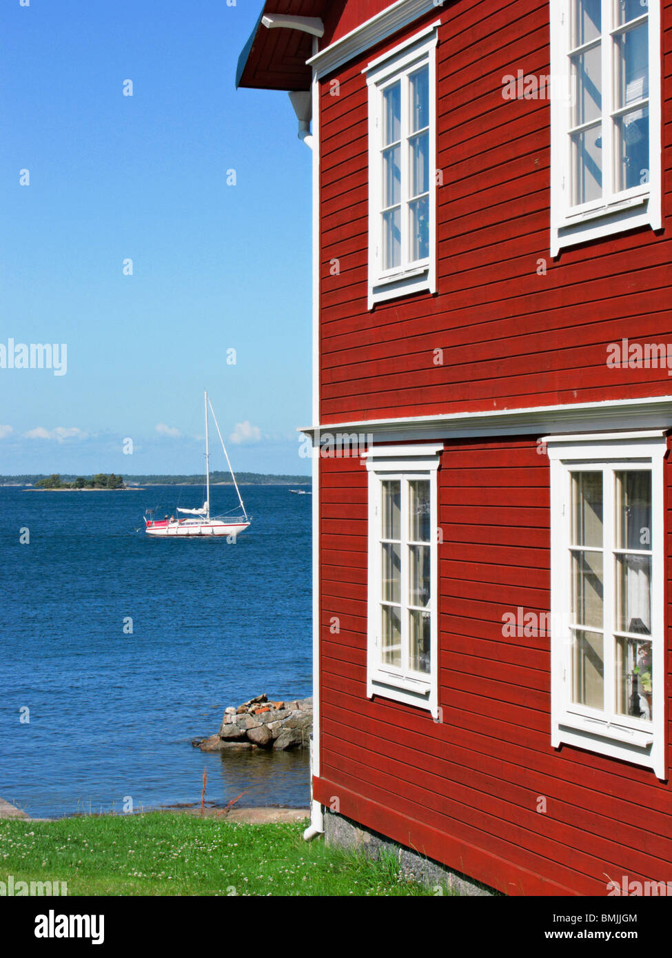 Scandinavia, Sweden, Stockholm, Sailing boat on sea with boathouse in foreground - Stock Image