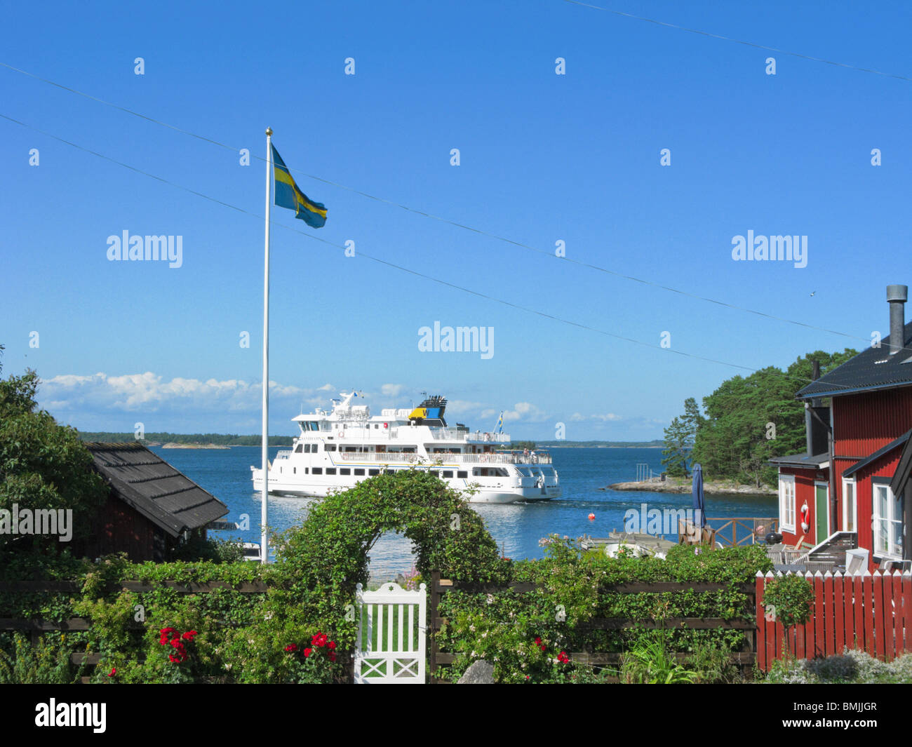 Scandinavia, Sweden, Stockholm, Sandhamn, View of ferry on sea with Swedish flag on foreground - Stock Image