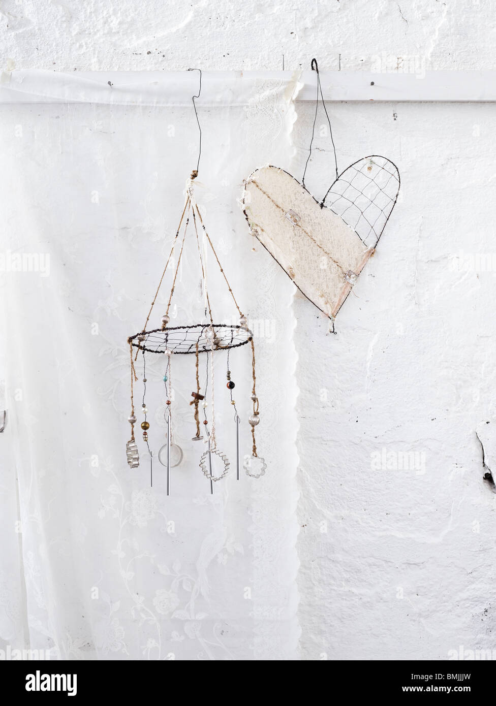 Scandinavia, Sweden, Stockholm, Heart shape and wind chime hanging against white wall - Stock Image
