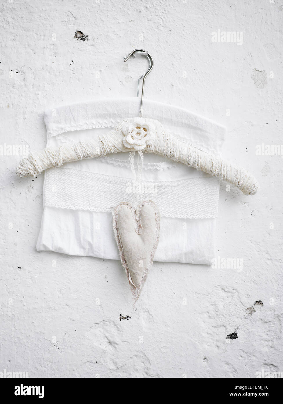 Scandinavia, Sweden, Stockholm, Coat hanger and heart shape hanging on white wall, close-up - Stock Image