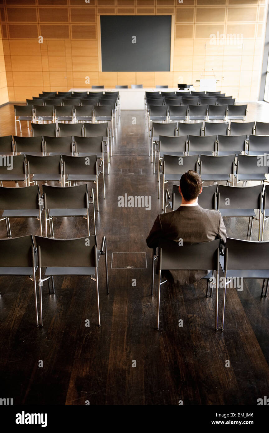 Businessman sitting at back of empty con - Stock Image