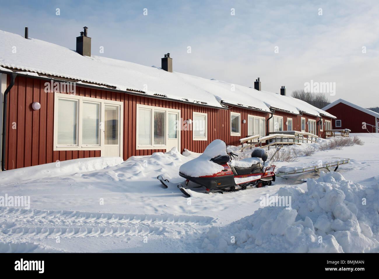 Scandinavia, Sweden, Harjedalen, Vemdalen, Snowmobile in front of house - Stock Image