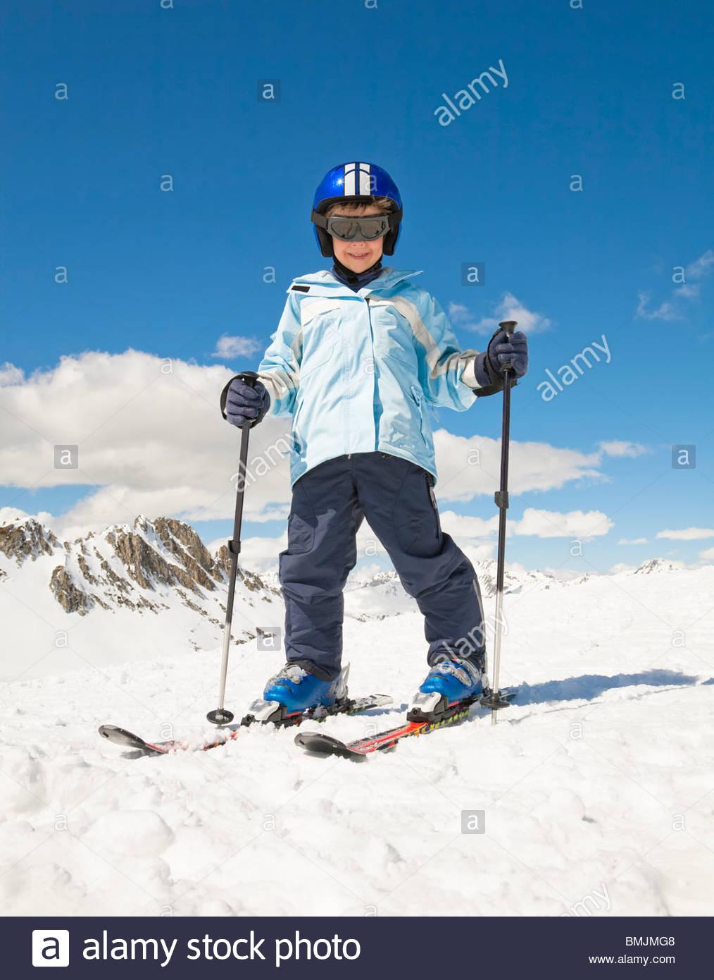 Boy skiing in snow, mountain backdrop - Stock Image