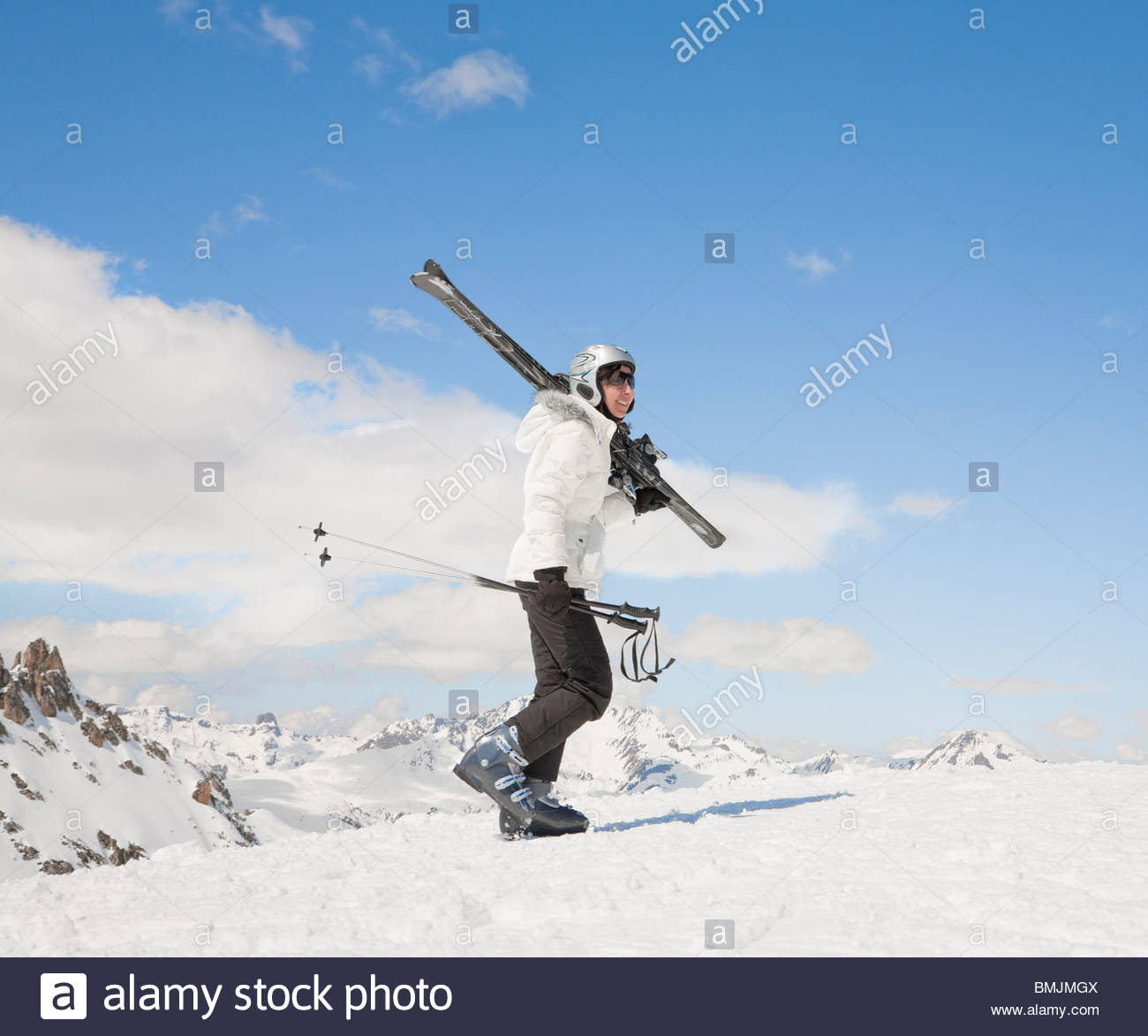 Woman walking up hill in snow, with skis - Stock Image