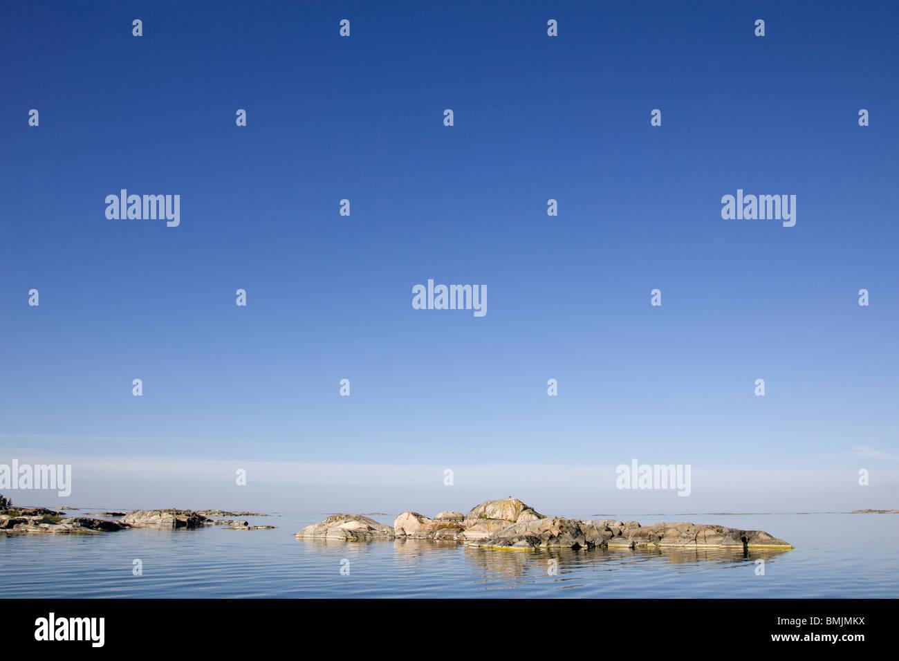 Flat rock in the ocean - Stock Image