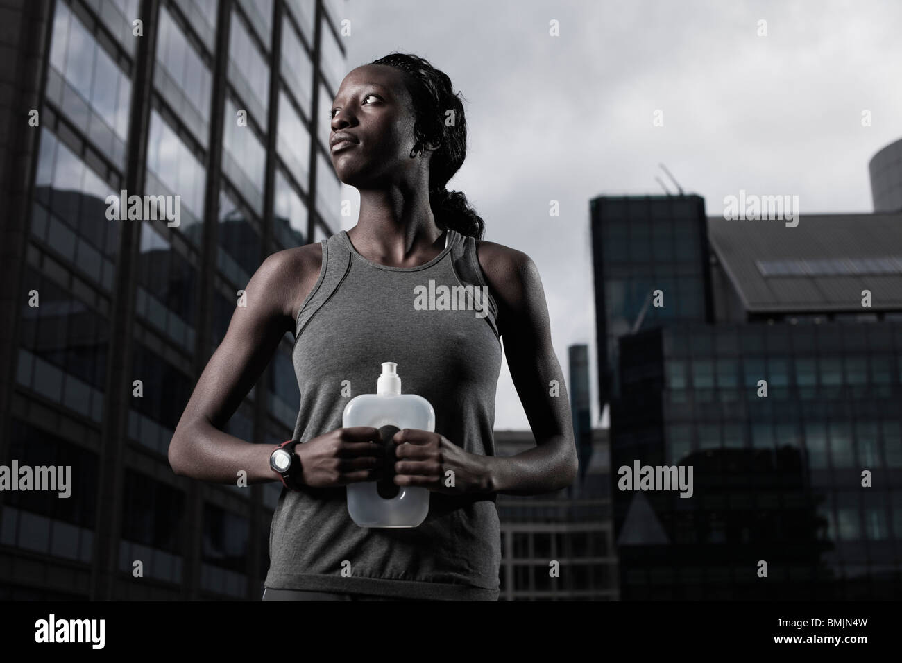 Fit young woman dressed in sportswear and holding water bottle backgrounded by modern city buildings - Stock Image