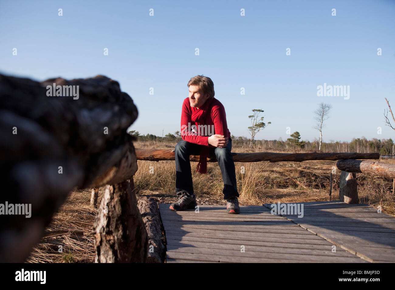 Man relaxing on wooden bench Stock Photo