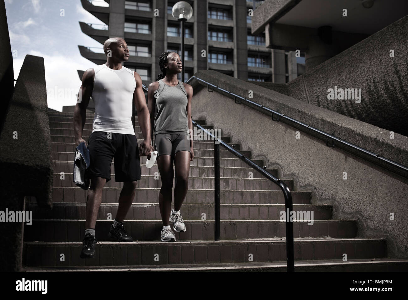 Young fit couple walking down stairway on city estate early morning - Stock Image
