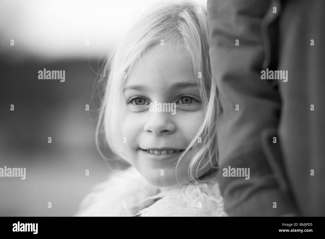 Scandinavia, Sweden, Vastergotland, Girl standing with father, smiling, close-up - Stock Image