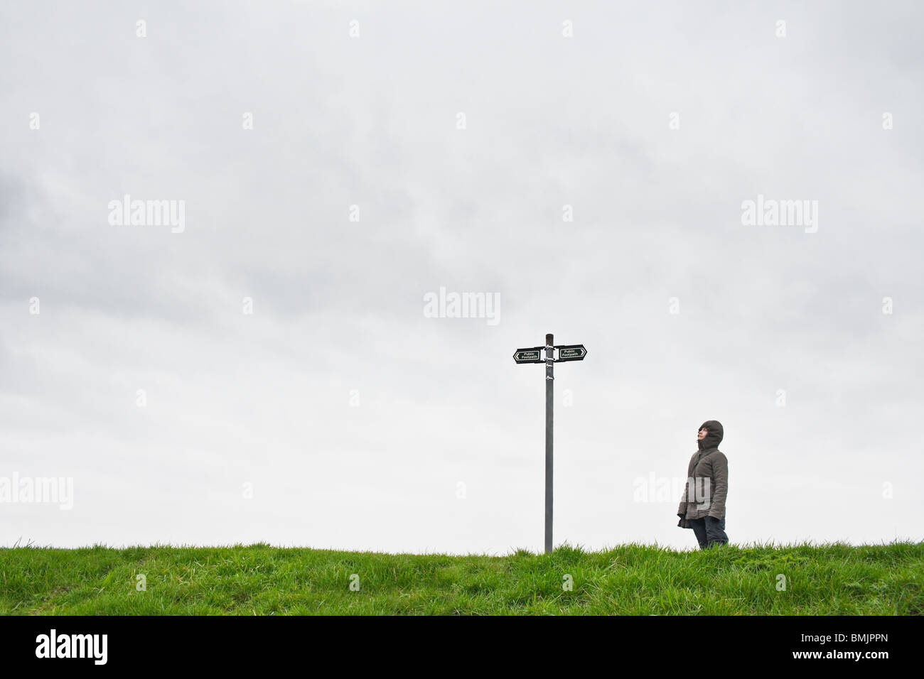 Woman looking up at sign post - Stock Image