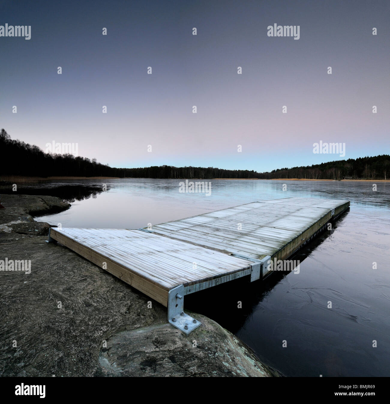 View of frost covered pier on lake Stock Photo