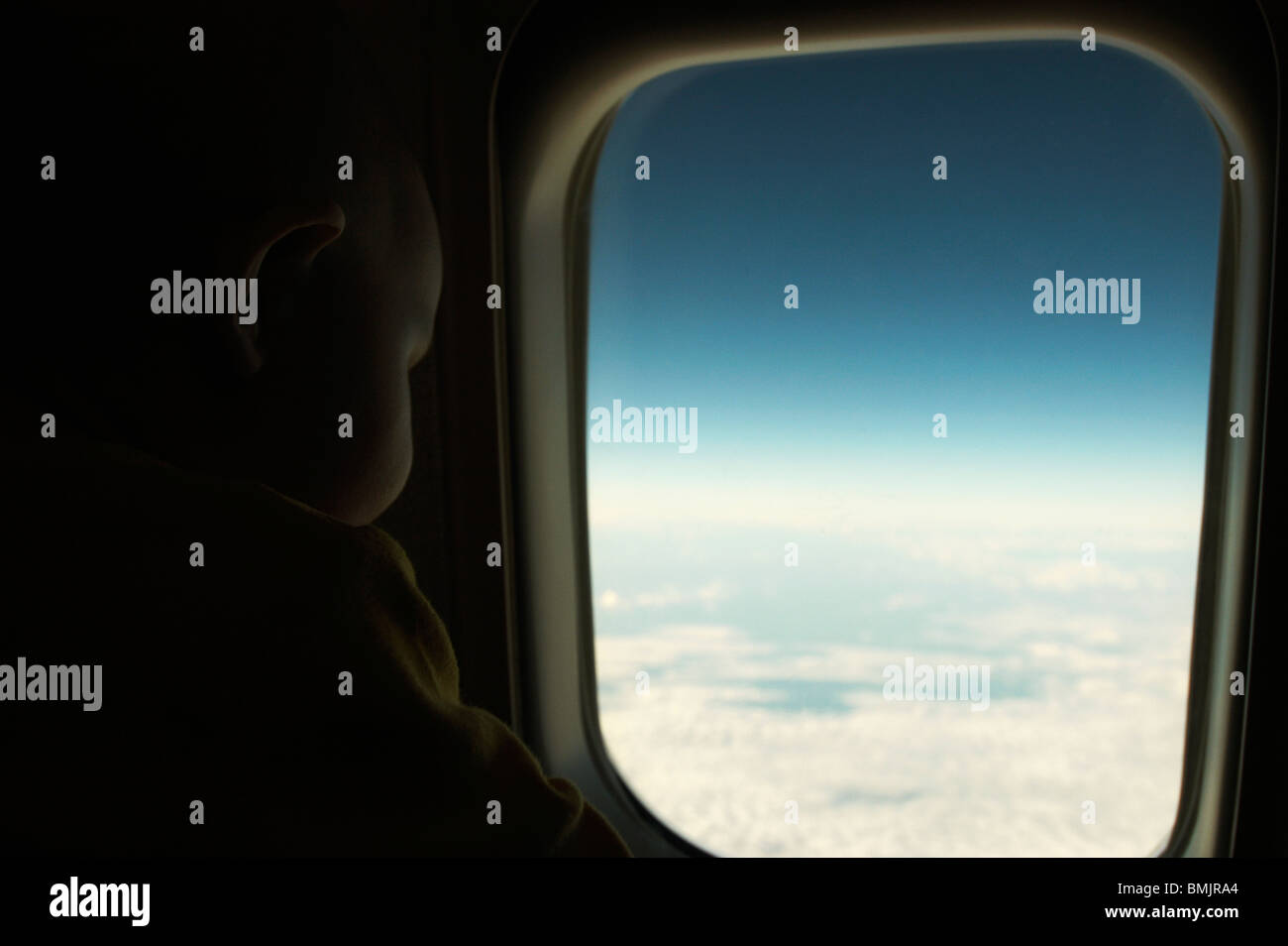 A baby looking out of a window in a plane Stock Photo
