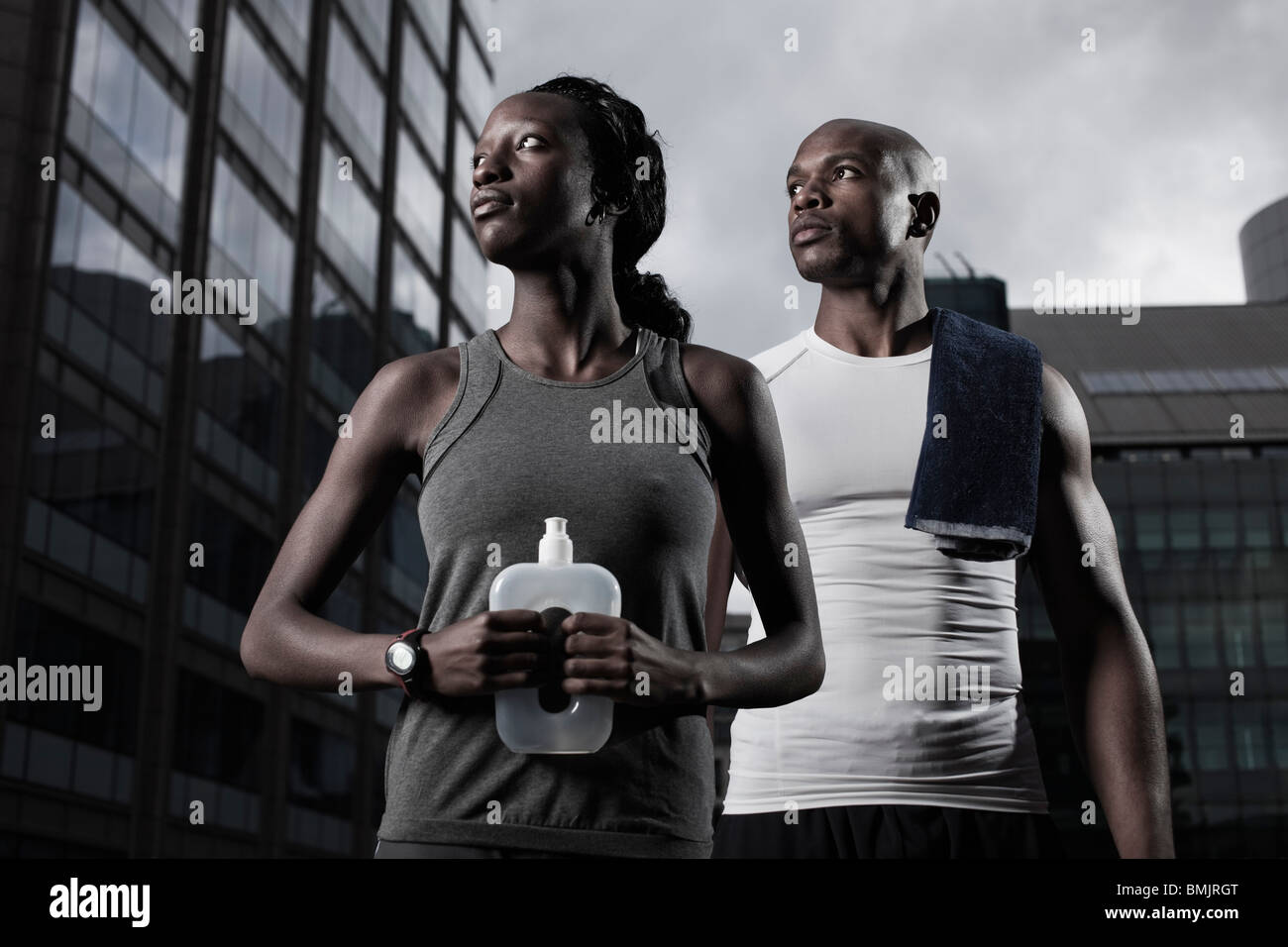 Athletic man and woman dressed in sportswear backgrounded by modern city buildings - Stock Image