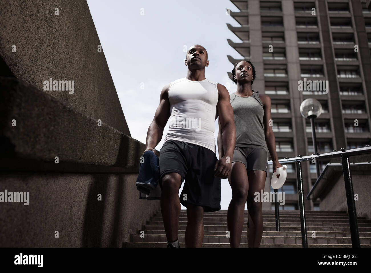 Fit young couple in running wear walking down steps on city estate - Stock Image