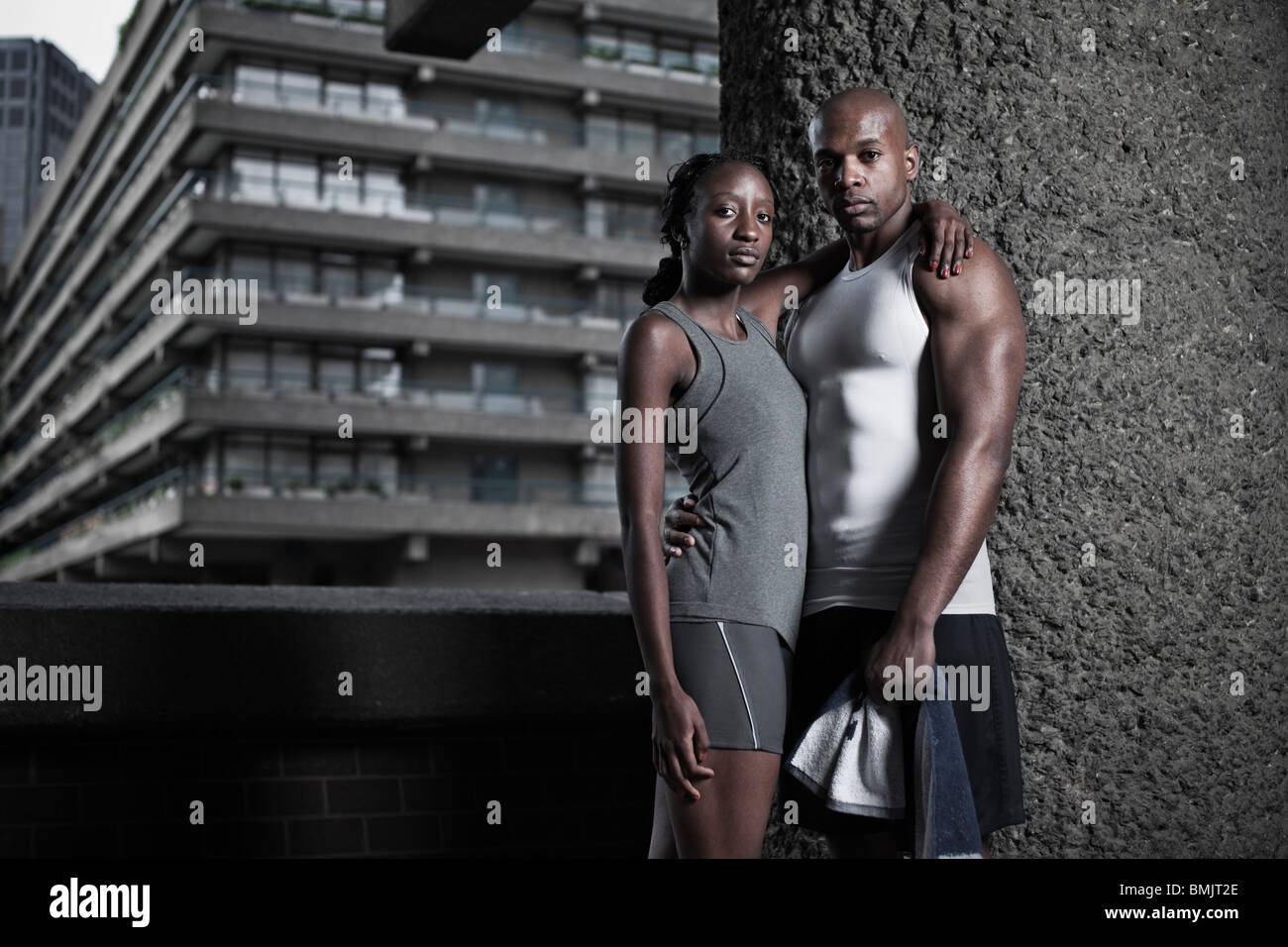 Portrait of athletic man and woman dressed in sportswear on city housing estate - Stock Image