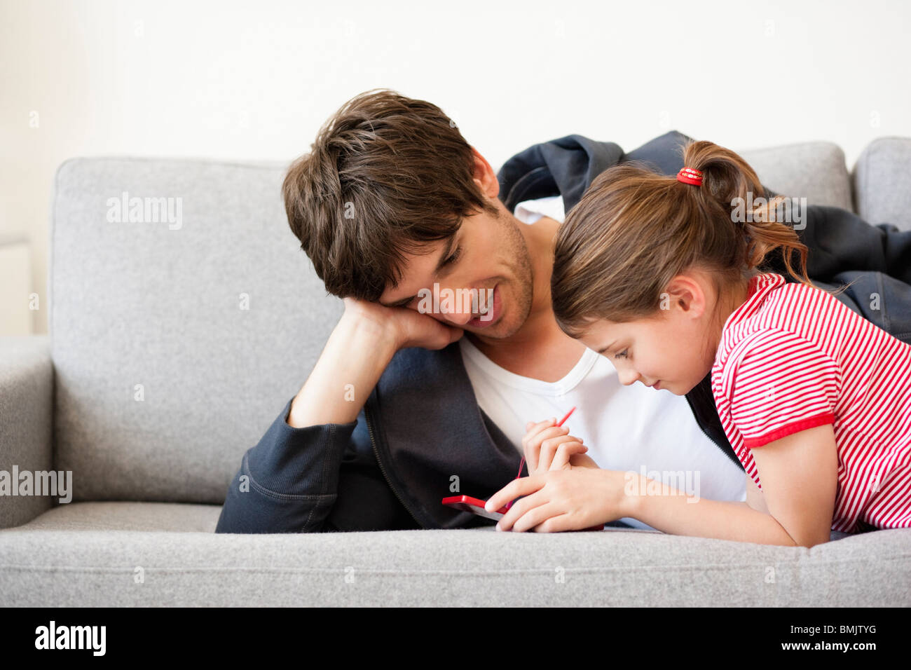 Father and girl playing video game Stock Photo