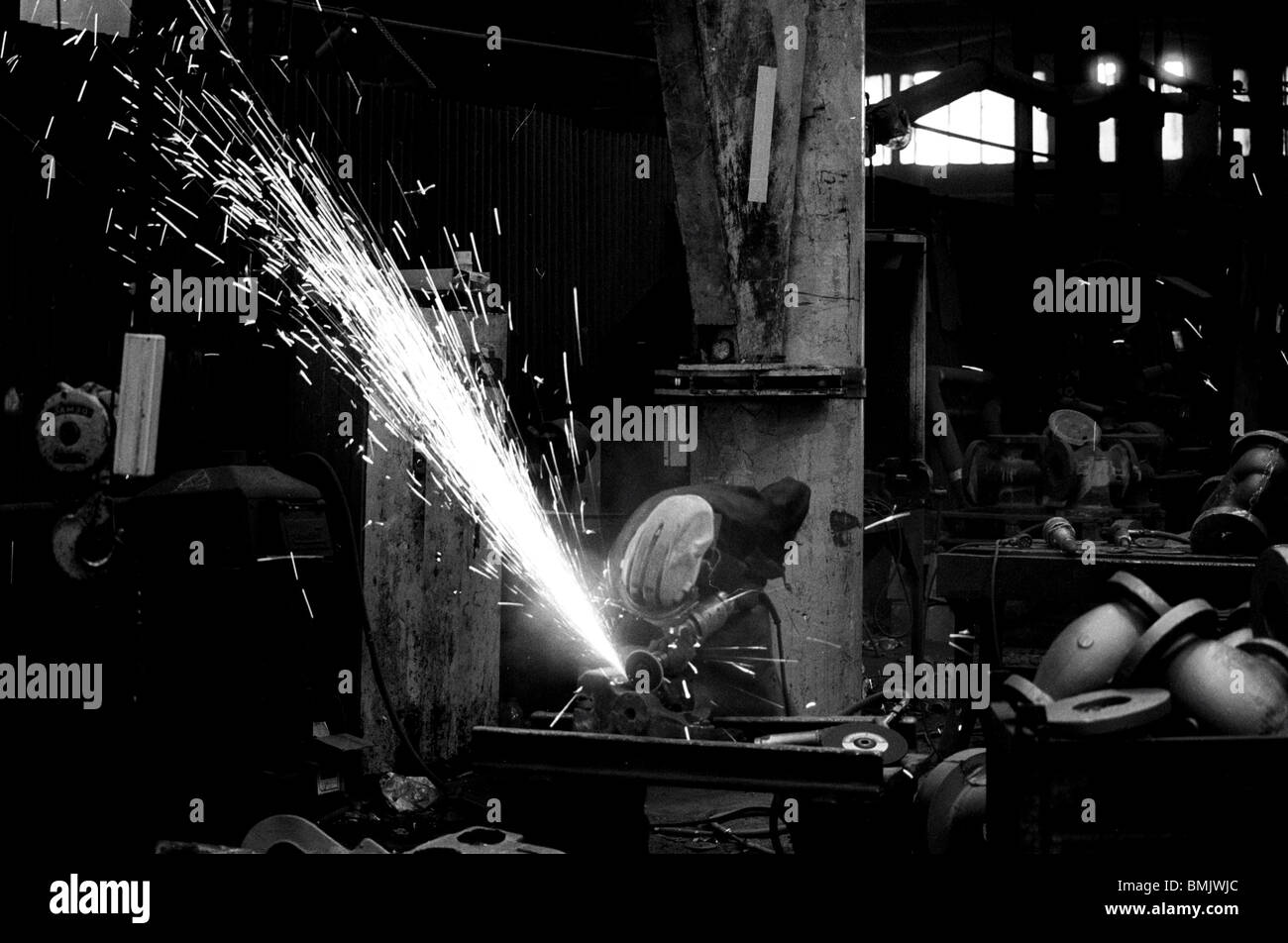 Worker using angle grinder in a Black Country foundry, Wednesfield, West Midlands, England - Stock Image