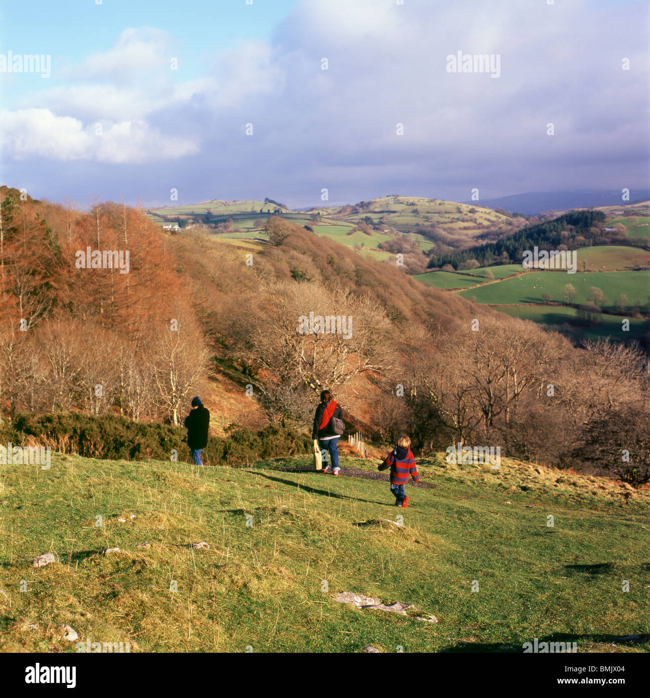 A young family walking down the hill in winter from a visit to Carreg Cennan Castle, Trapp, Wales, UK - Stock Image