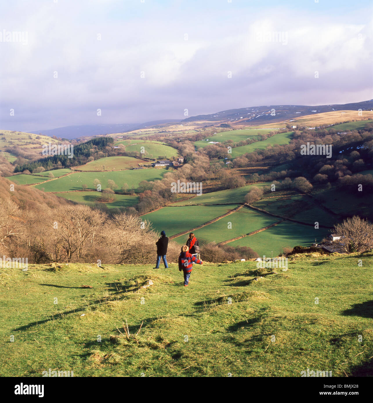 A young family walking down the hill in winter from a visit to Carreg Cennan Castle, Trapp, Wales, UK  KATHY DEWITT - Stock Image