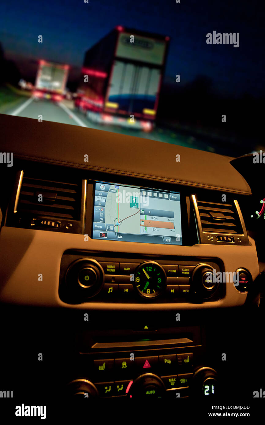 Interior of Range Rover car showing sat nav and dials on dashboard at night on motorway with traffic. UK - Stock Image