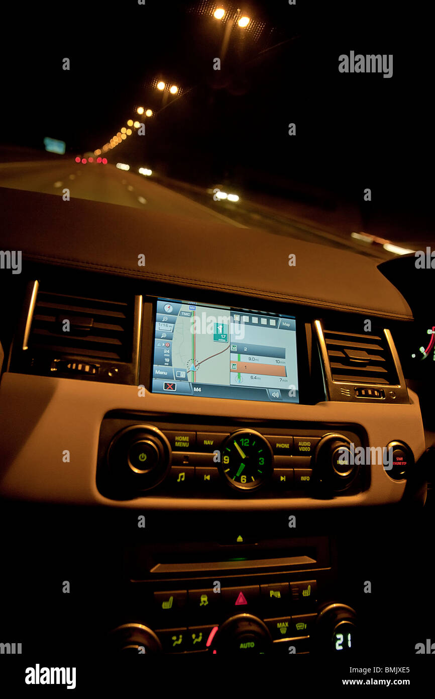 Interior of Range Rover car showing sat nav and dials on dashboard at night on motorway. UK - Stock Image