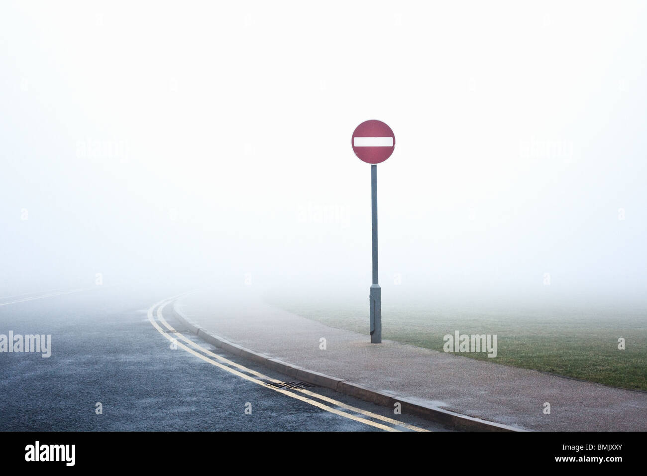 Road with no entry sign in fog - Stock Image