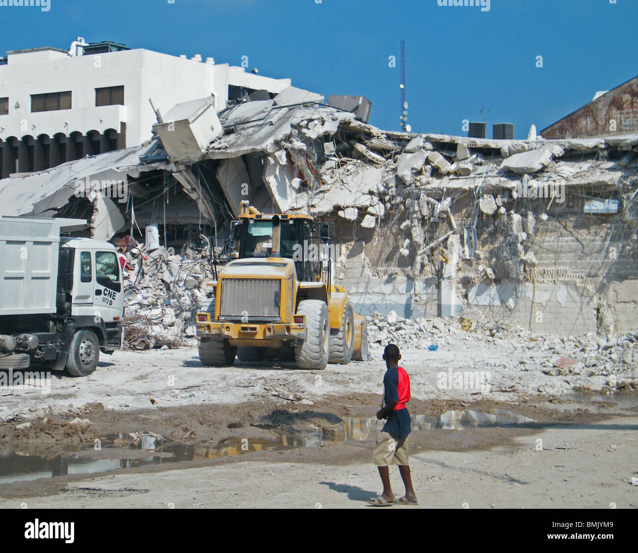A young boy watches as diggers and trucks remove rubble from central Port au Prince after the Haiti earthquake - Stock Image
