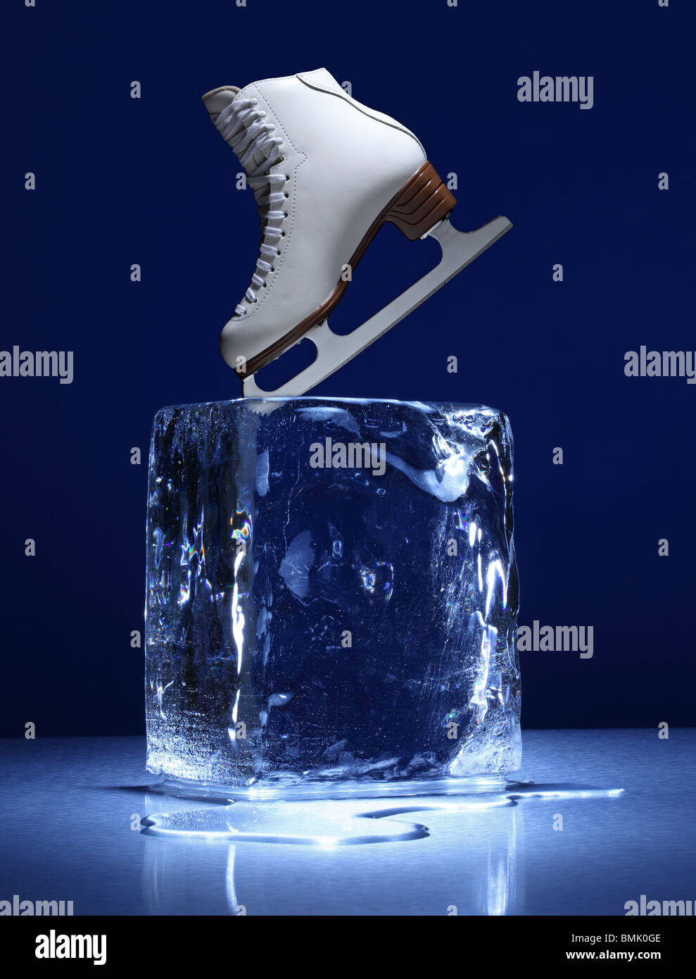 A frozen block of ice with a white ice skate on a metal surface - Stock Image