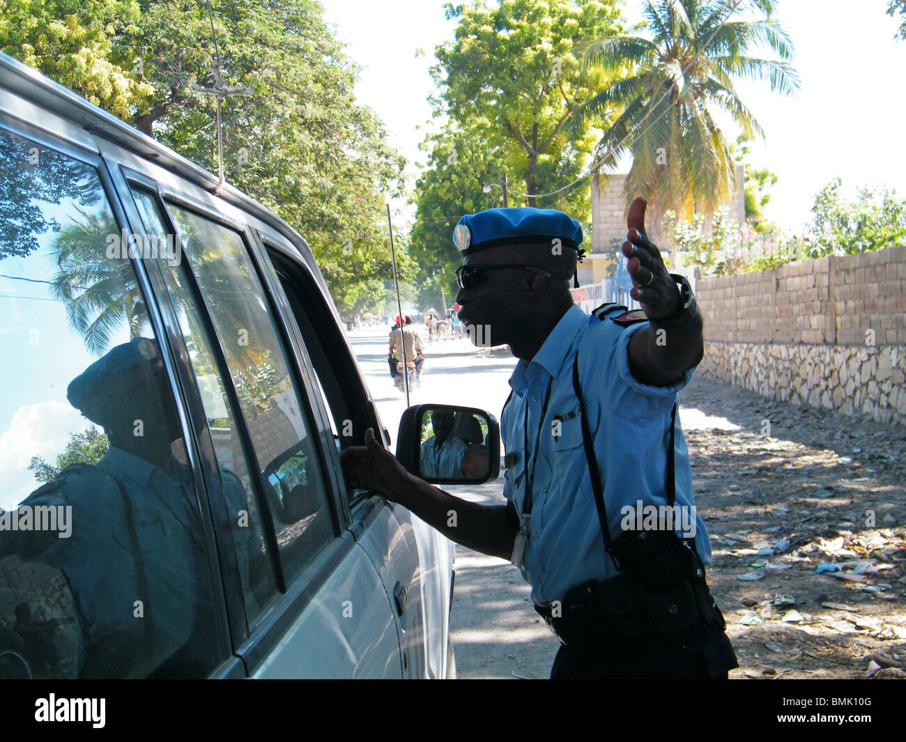 A Haitian policeman stops a driver at a roadblock on the outskirts of Gonaives, Haiti - Stock Image
