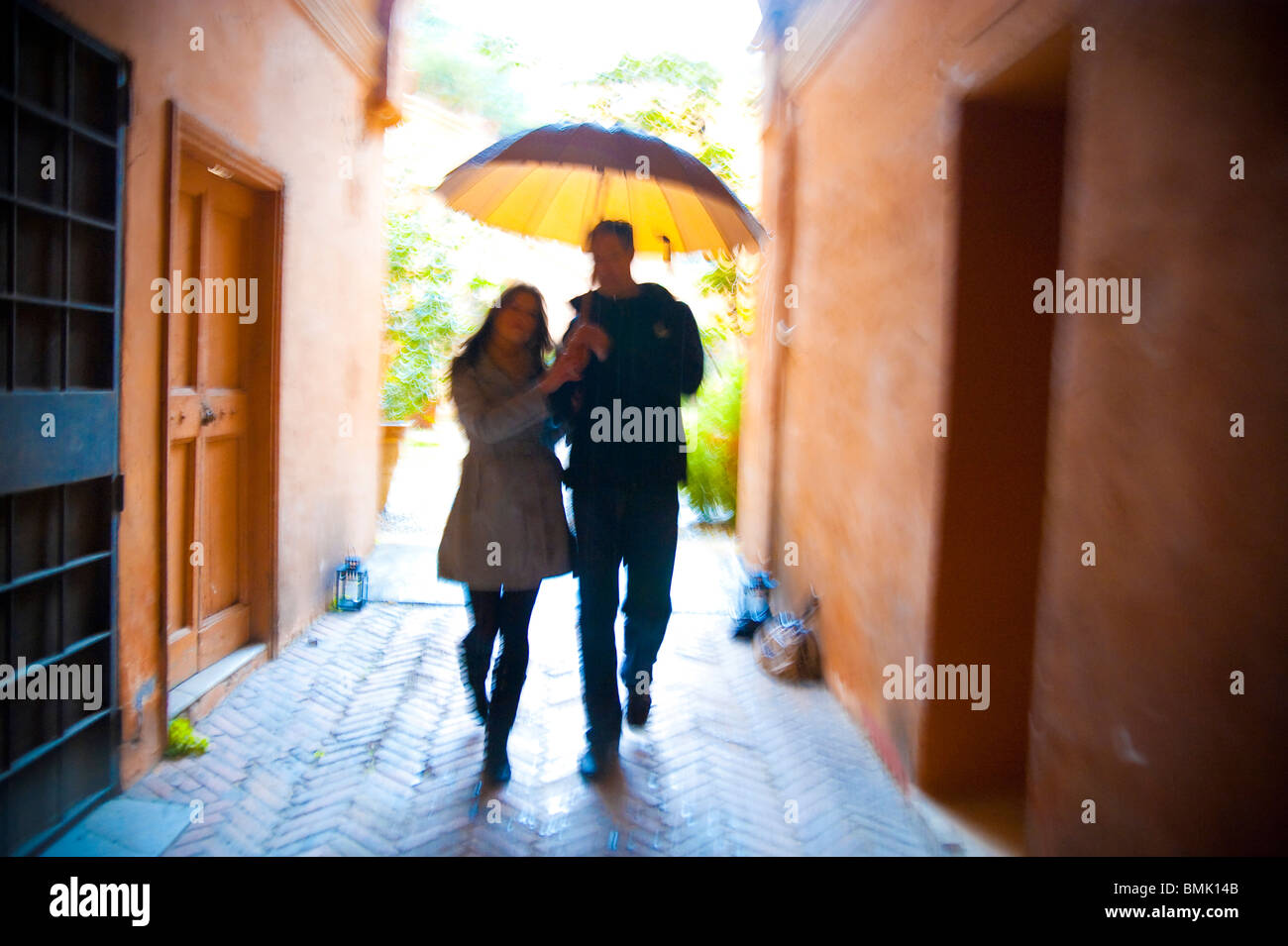 Couple with motion blur walking together with an umbrella under the rain in Rome Italy - Stock Image