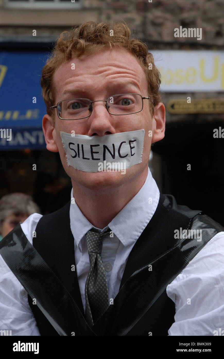 A performer with his mouth taped publicizing his show from the Edinburgh Fringe Festival. - Stock Image