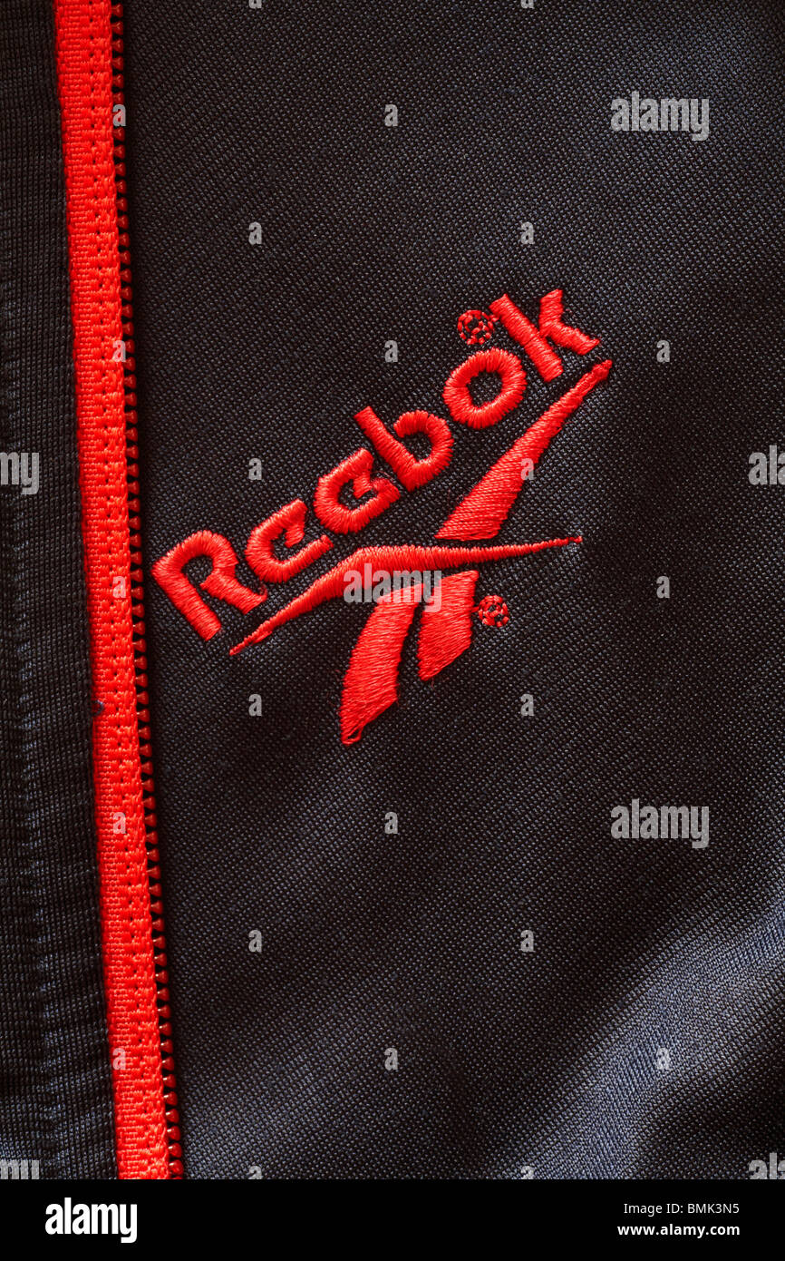 red Reebok logo on black tracksuit top with red matching zip - Stock Image