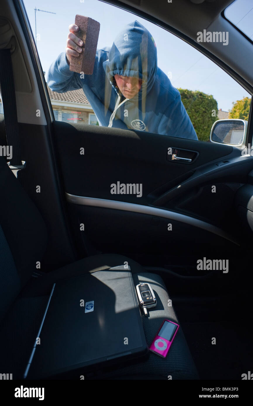 A MODEL RELEASED man about to break into a car to steal a laptop computer , a phone and an ipod in the Uk - Stock Image