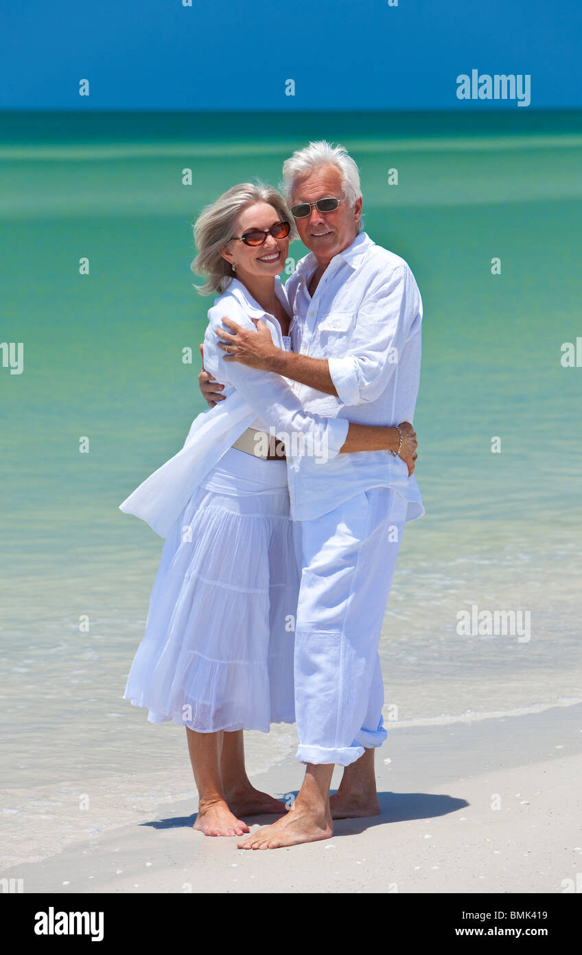69f2577a9c5a Romantic and happy senior man and woman couple dressed in white and  embracing on a deserted tropical beach
