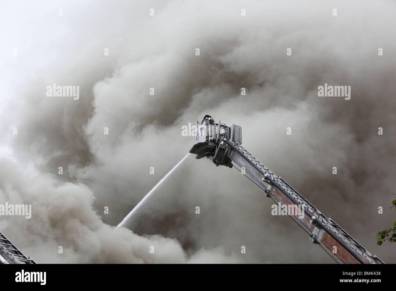 firefighter battling a smoky blaze Stock Photo