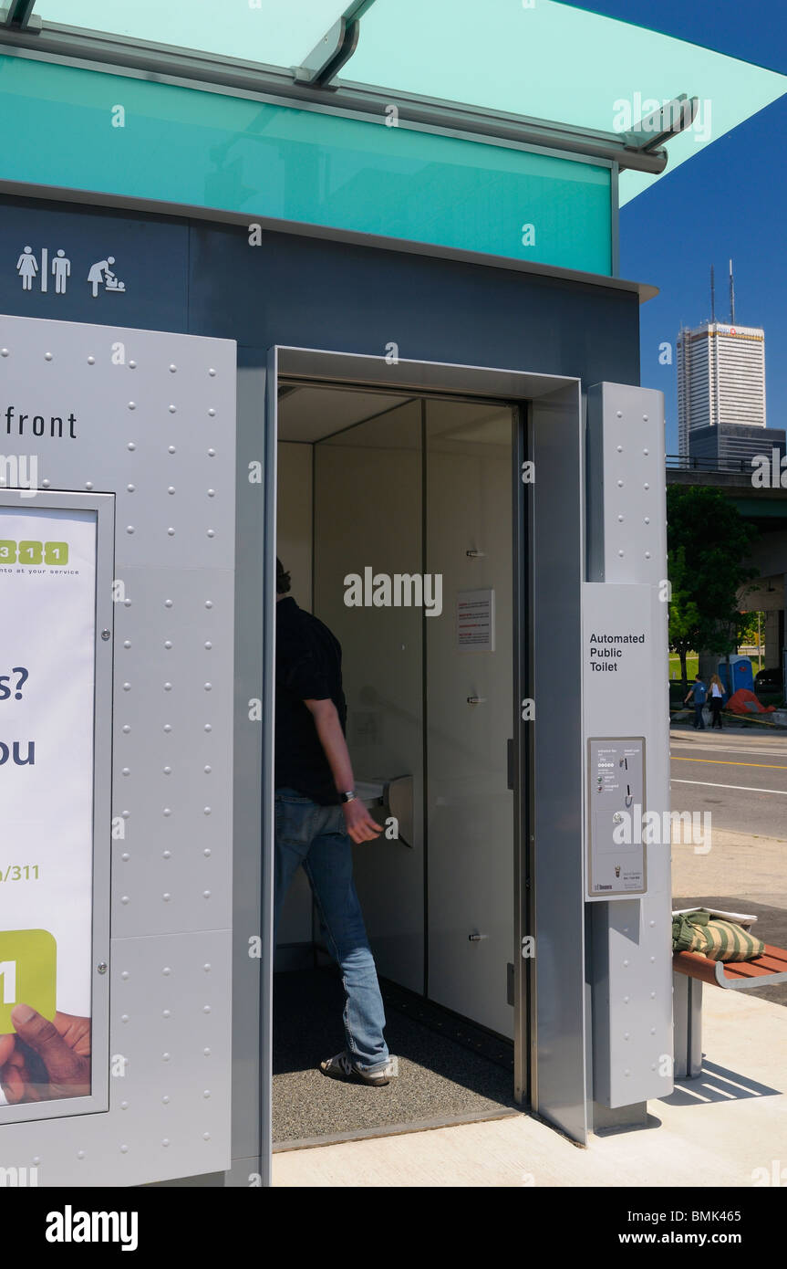 Man entering first new modern automated public pay toilet on the Toronto waterfront - Stock Image