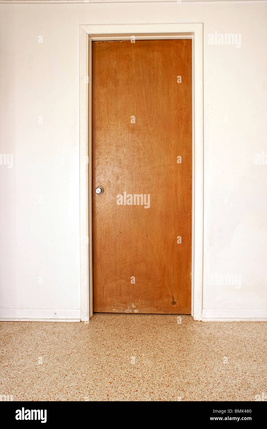 A Closed Wooden Door On A White Wall Terrazzo Floor Stock