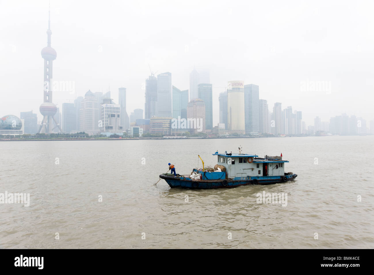 Small boat scooping up litter on the Huangpu River, Shanghai, China Stock Photo