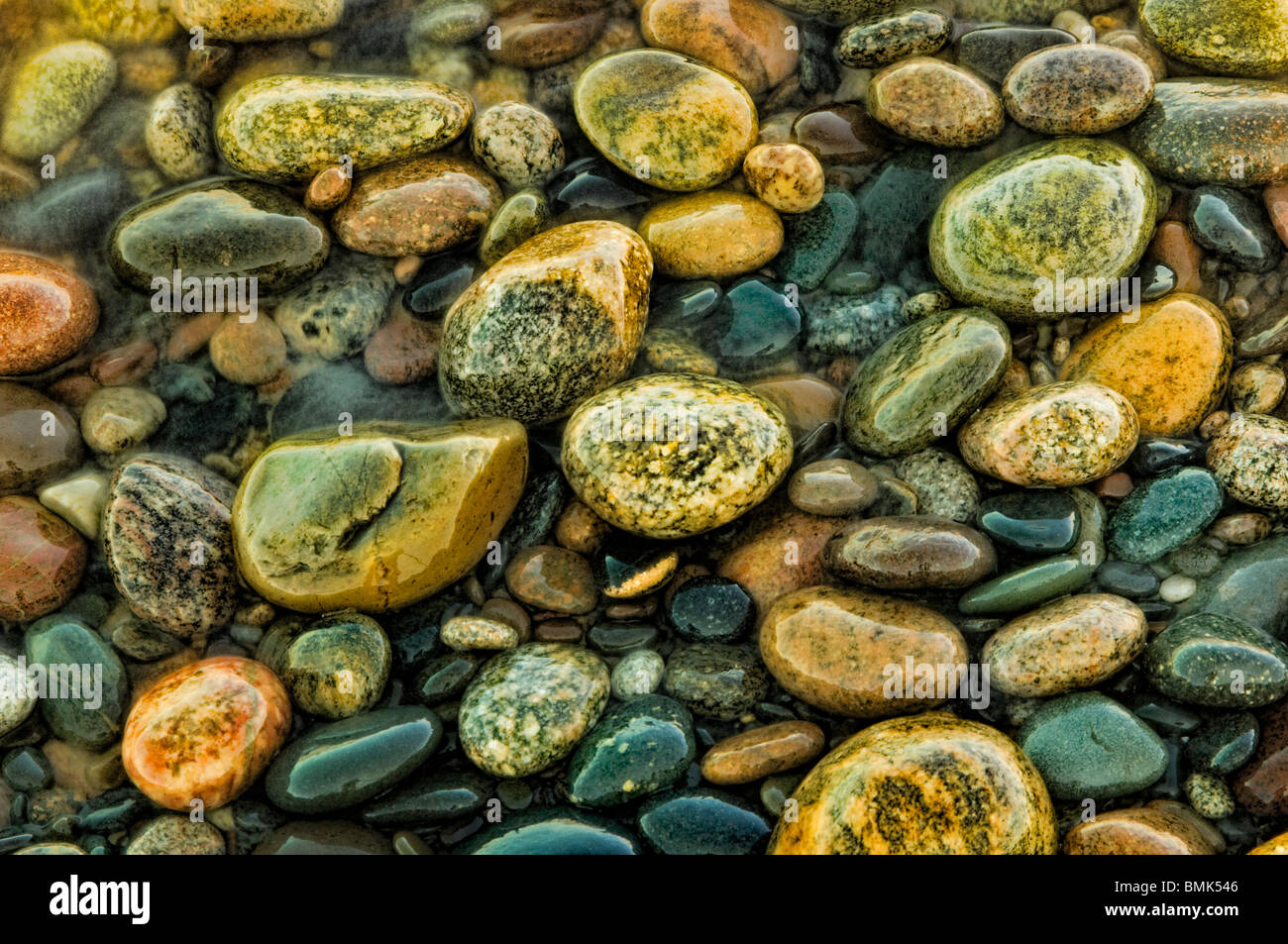 Colorful beach stones along the shores of Lake Superior in this Little Traverse Conservancy nature preserve - Stock Image