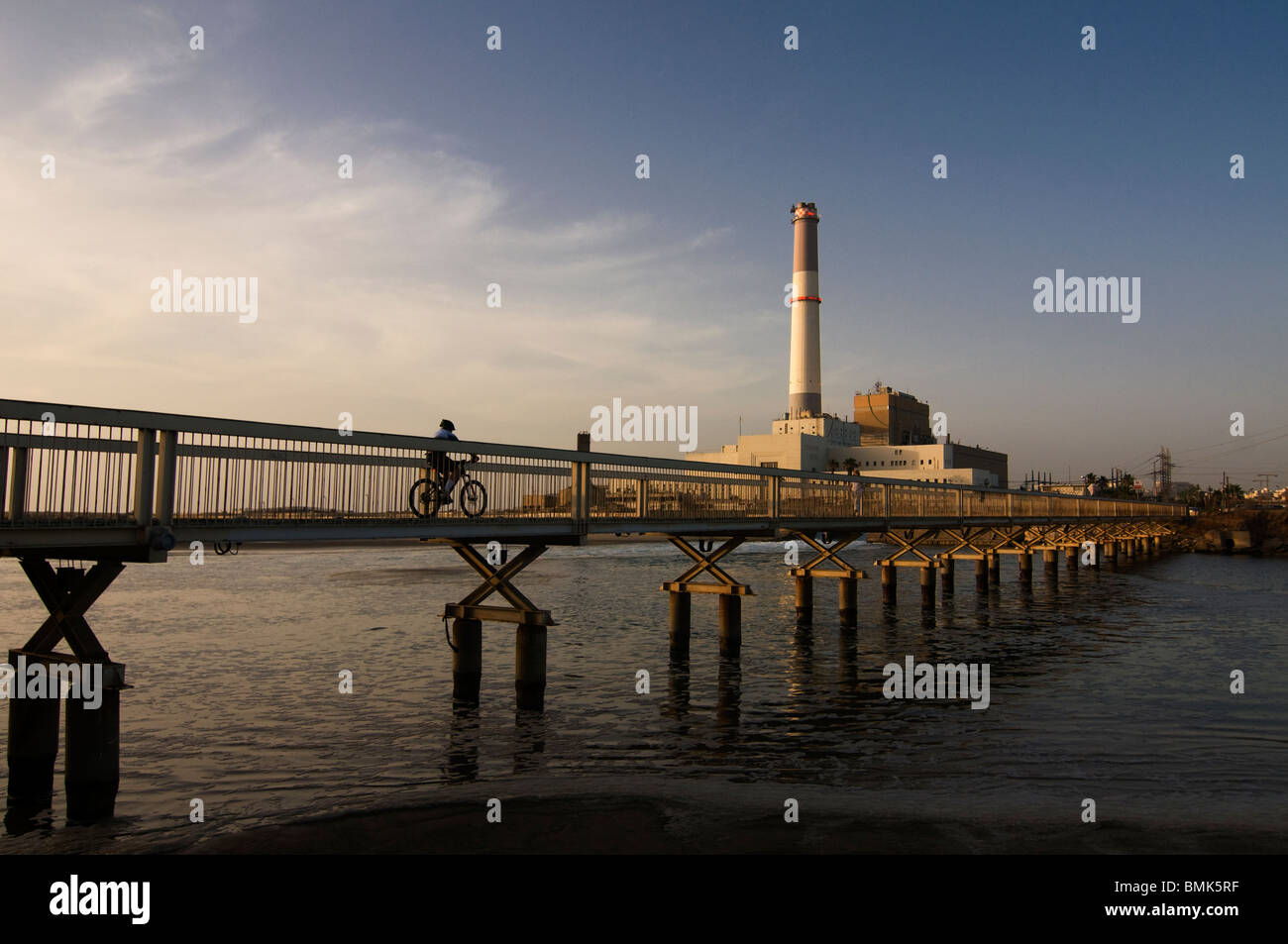 Bicycler crossing a bridge over the Yarkon or Yarqon river near Reading power station supplying electrical power - Stock Image