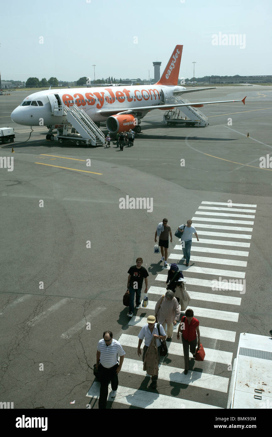 Passengers disembarking from an airplane - Stock Image