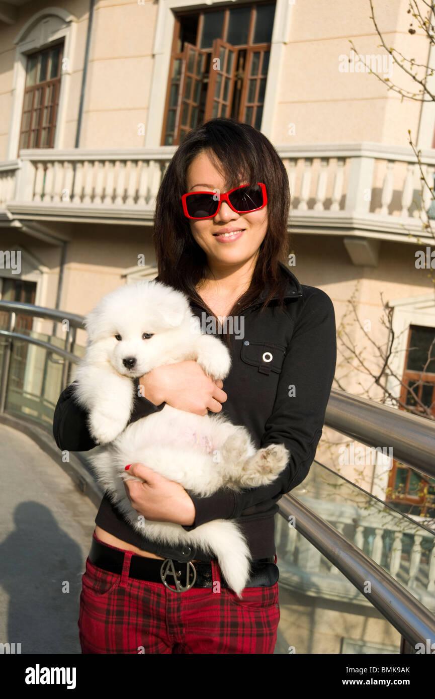 Fashionable young woman holding her pet pedigree dog, Shanghai, China - Stock Image
