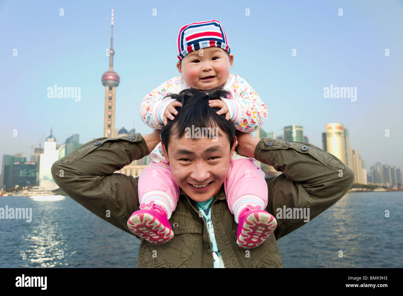 Father and single child on the waterfront, Shanghai, China - Stock Image