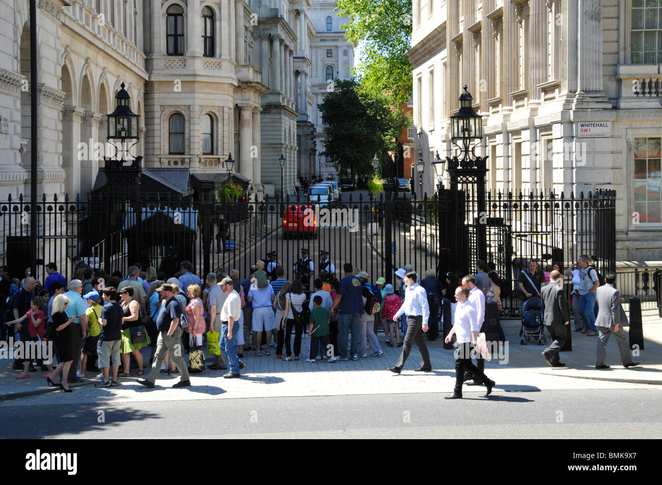 Tourists on the Whitehall side of Downing Street in front of steel security gates controlled by Metropolitan police Stock Photo