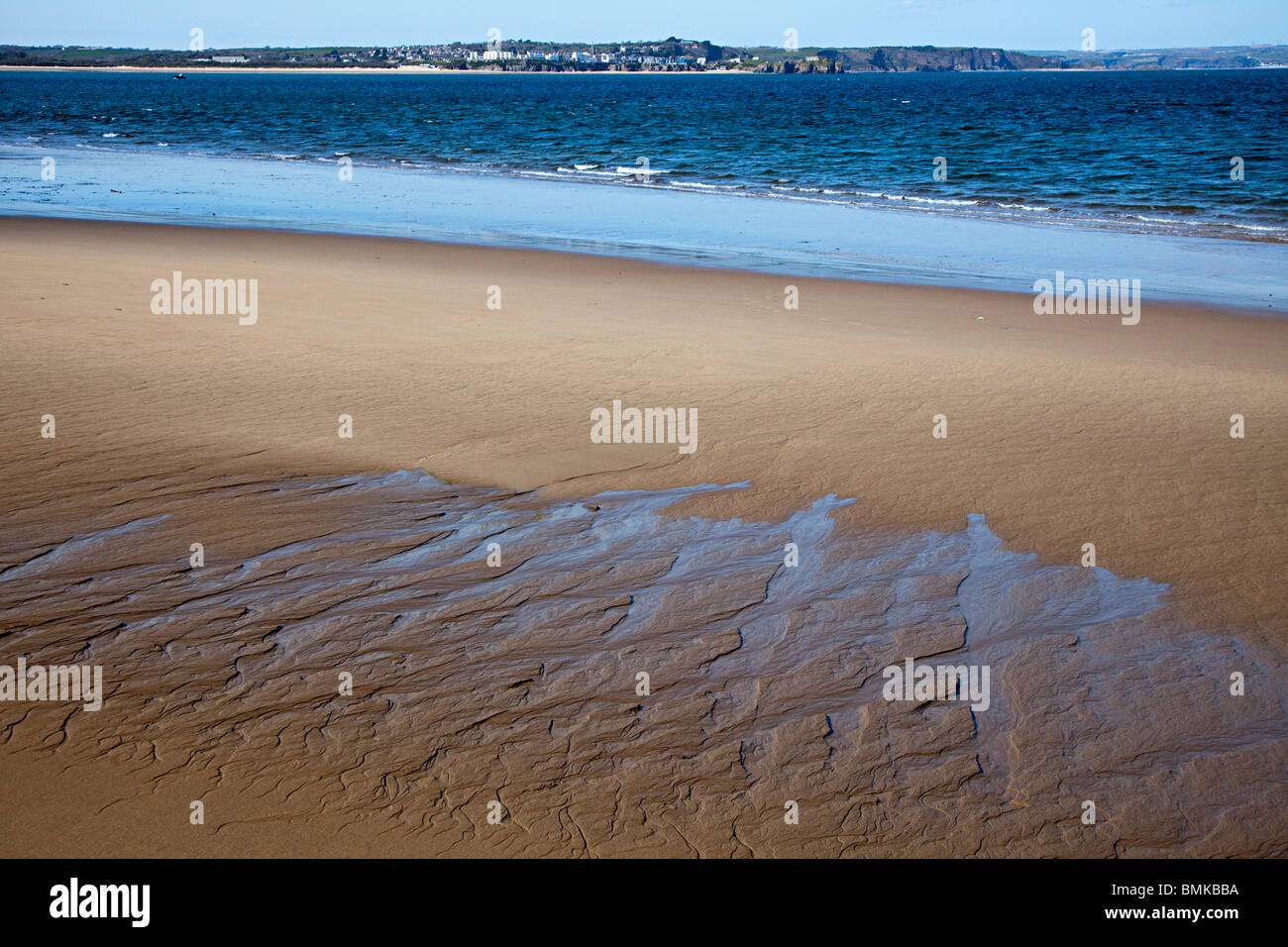 Ripples in sand on beach on Caldey Island with Tenby in distance Wales UK - Stock Image