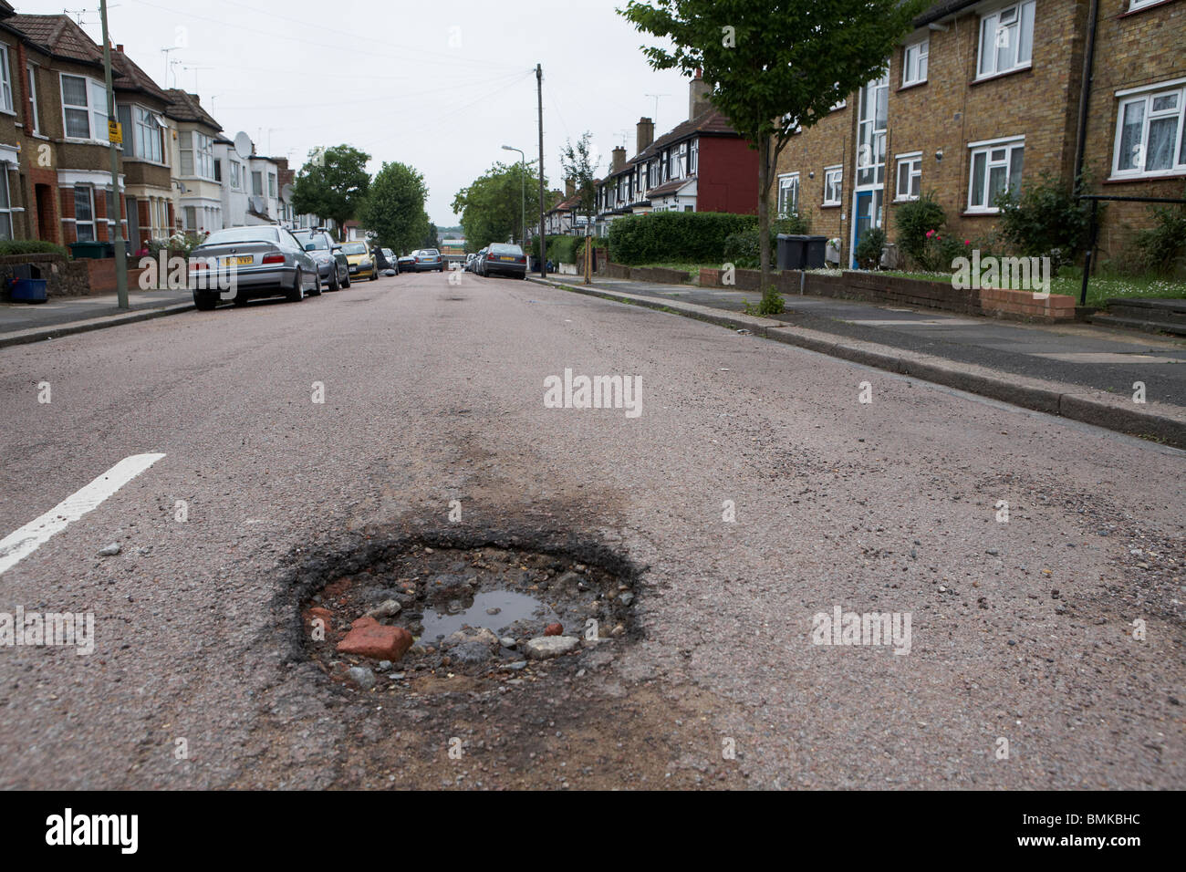Pot holes in a suburban road in North London - Stock Image