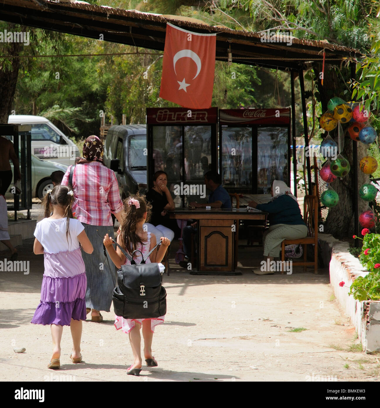 Turkish schoolgirls walking into a cafe at Camel Beach on Kargi Bay close to Bodrum on the Aegean Sea Turkey - Stock Image