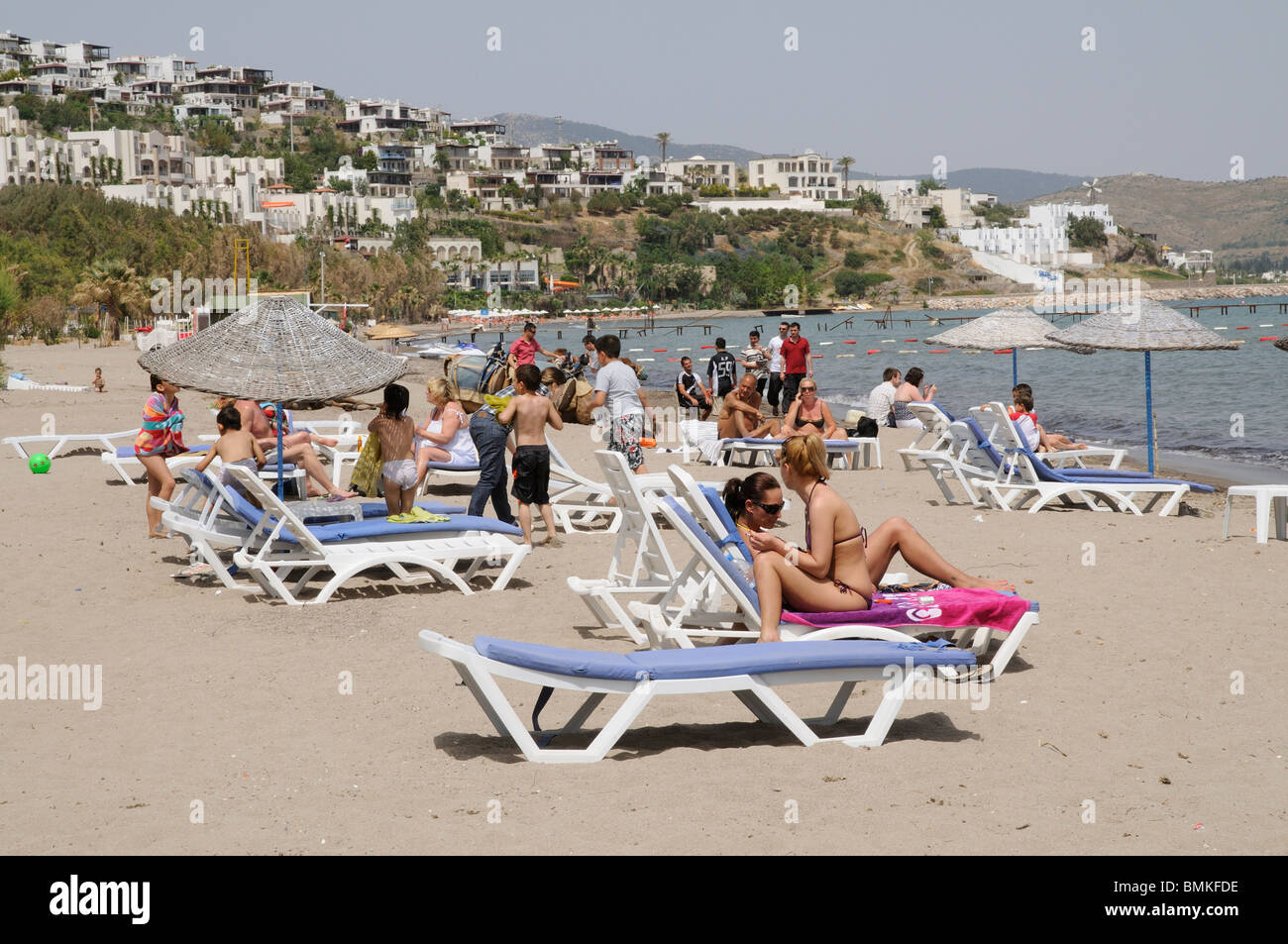 Holidaymakers on the beach at Camel Beach a seaside resort close to Bodrum south west Aegean Turkey Asia Minor - Stock Image